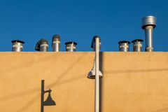 Pipes on a Rooftop. Pipes on a roof and shadows on a wall royalty free stock images