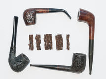 Pipes  and tobacco. Four old wooden smoking pipes and pieces of pressed tobacco close-up on white Stock Image