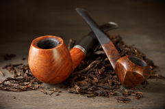Pipes on tobacco pile Stock Photo