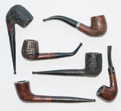 Pipes on white. Six old wooden smoking pipes close-up on white Stock Images