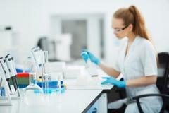 Pipeta que cae una muestra en un tubo de ensayo Ayudante de laboratorio que analiza sangre en laboratorio Ayuda, prueba del VIH Fotos de archivo