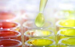 Pipetta del laboratorio con una goccia della sostanza sopra le provette Fotografia Stock
