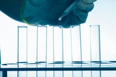 Pipette adding fluid in to test tubes Stock Photos
