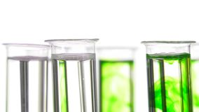 Pipette depositing drops of green dye in rotating test tubes. Closeup of test tubes on white background stock footage