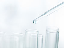 Pipette dripping in empty test tubes Royalty Free Stock Image