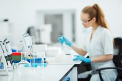Pipette dropping a sample in a test tube. Laboratory assistant analyzing blood in lab. Aids, hiv test Stock Photos