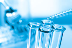 Pipette and test tube on blue background Royalty Free Stock Images