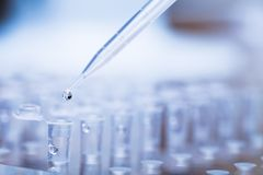 Free Pipette Tip With Droplet Over Rack Of Test Tubes Stock Images - 25087684