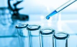 Pipette und Reagenzglas auf blauem Hintergrund Lizenzfreie Stockfotografie