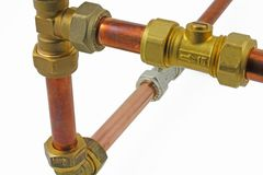 Pipework close up. Copper pipe with compression fittings on top of blurred pipework on an white background royalty free stock photos