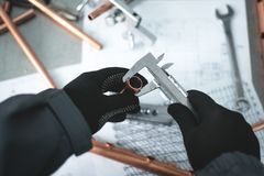 Pipework. Engineer is holding in hands a brass pipe and is measuring a diameter by a calipers. Pipework royalty free stock photo