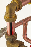 Pipework. Isolated copper pipe with compression fittings on top of blurred pipework on an white background royalty free stock image