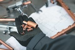 Pipework. Worker is holding in hands a brass pipe trimming on a fitter workbench background. Pipework stock photography