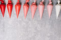 Piping bags. With colors range from white to red, with different gradation over a gray background royalty free stock photo