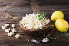 A pipoca caseiro fresca crocante salgado flavored com casca de limão e os alecrins scent em uma bacia de madeira no fundo simples foto de stock royalty free