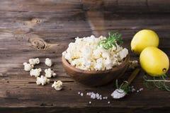 A pipoca caseiro fresca crocante salgado flavored com casca de limão e os alecrins scent em uma bacia de madeira no fundo simples fotos de stock