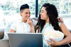 Pipoca de alimentação da mulher a seu sócio ao usar o portátil Imagens de Stock Royalty Free