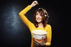 Pipoca de jogo de sorriso da jovem mulher que olha acima com sorriso largo imagem de stock royalty free