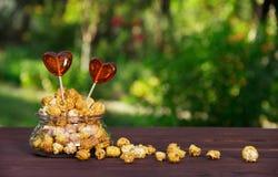 A pipoca e os doces do caramelo em um coração dão forma lollipops Conceito romântico Conceito festivo Foto de Stock