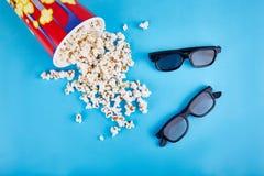 Pipoca e vidros 3d em um fundo azul O conceito é recreação, cinema Imagens de Stock Royalty Free