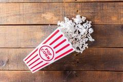Pipoca na caixa clássica do serviço do cinema no fundo de madeira da Foto de Stock Royalty Free