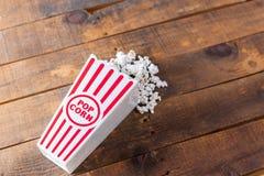 Pipoca na caixa clássica do serviço do cinema no fundo de madeira da Fotografia de Stock Royalty Free