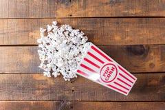 Pipoca na caixa clássica do serviço do cinema no fundo de madeira da Fotos de Stock Royalty Free
