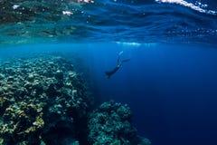 Piqué libre d'homme de plongeur dans l'océan, vue sous-marine avec des roches et coraux photo libre de droits