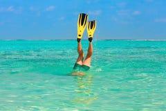 Piqué d'hommes naviguant au schnorchel dans l'eau claire avec les nageoires jaunes Photos stock