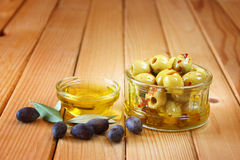 Piquant olives with a spicy chilli seasoning over wooden background Stock Images