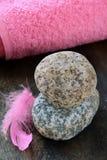 Pique la pluma en las piedras y la toalla rosada Fotografía de archivo libre de regalías