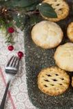 Pique las empanadas en una bandeja con las decoraciones festivas de la Navidad Fotos de archivo