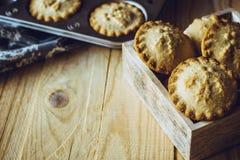 Pique las empanadas en una caja y una bandeja de madera de la hornada en el fondo, en una tabla de cocina, entonada en estilo del Imagenes de archivo