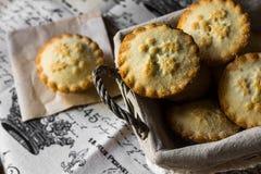 Pique las empanadas en una cesta en el paño de lino del vintage, una empanada en un pedazo de papel de cera, la visión superior,  Imagen de archivo