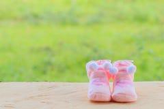 Pique los calcetines hechos punto para el bebé en el de madera, en backgro verde Fotos de archivo libres de regalías