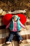 Pique-nique d'automne, une petite fille avec un coeur de rouge de jouet Photos stock