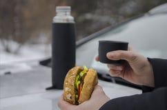 Pique-nique d'hiver avec le thé et l'hamburger sur le capot d'une voiture argentée dans la perspective de la forêt photographie stock libre de droits