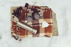 Pique-nique d'hiver sur la neige Coeur chaud de thé, de thermos et de boule de neige sur la couverture chaude confortable Photographie stock