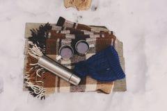 Pique-nique d'hiver sur la neige Coeur chaud de thé, de thermos et de boule de neige sur la couverture chaude confortable Photos stock