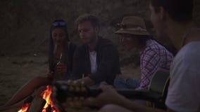 Pique-nique des jeunes avec le feu sur la plage le soir Amis gais chantant des chansons et jouant la guitare banque de vidéos
