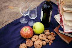 Pique-niquez dans l'herbe avec la nourriture et le vin savoureux Image stock