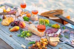 Pique-niquez sur la plage au coucher du soleil dans le style de boho Dîner romantique, ami Photo stock