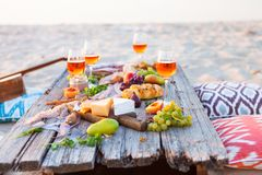 Pique-niquez sur la plage au coucher du soleil dans le style de boho Dîner romantique, ami Photos stock