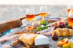 Pique-niquez sur la plage au coucher du soleil dans le style de boho Dîner romantique, ami Images stock