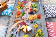 Pique-niquez sur la plage au coucher du soleil dans le style de boho Dîner romantique, ami Photos libres de droits