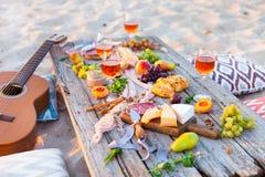 Pique-niquez sur la plage au coucher du soleil dans le style de boho Dîner romantique, ami Image libre de droits