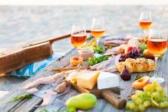 Pique-niquez sur la plage au coucher du soleil dans le style de boho Dîner romantique, ami Photographie stock libre de droits