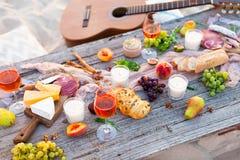 Pique-niquez sur la plage au coucher du soleil dans le style de boho Dîner romantique, ami Photographie stock