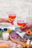 Pique-niquez sur la plage au coucher du soleil dans le style de boho Dîner romantique, ami Photo libre de droits
