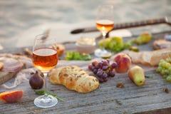 Pique-niquez sur la plage au coucher du soleil dans le style de boho, nourriture et buvez concentré Photo stock